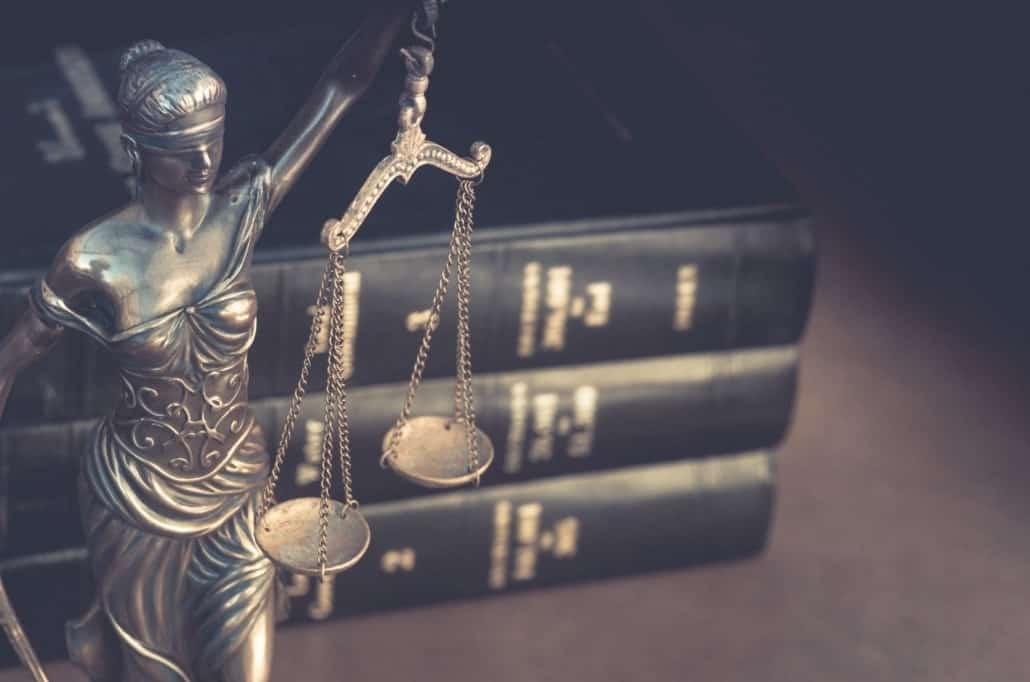 The Lady Justice statue stands next to family law and estate planning law books.