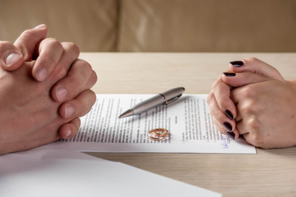 Two rings sit on top of a divorce form with two ex spouses discussing alimony