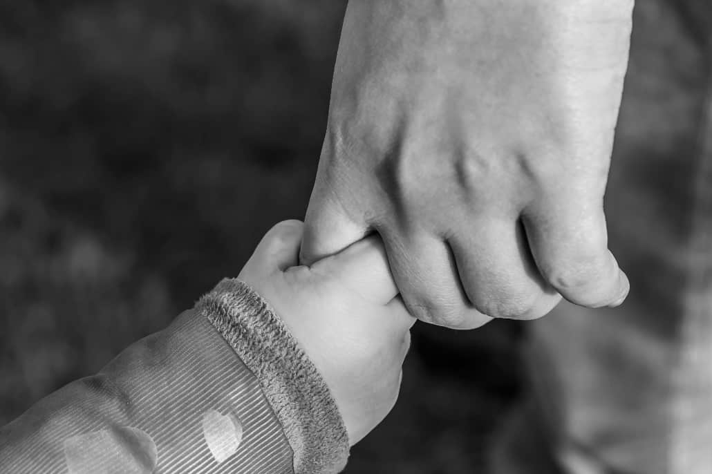 A grandparent holds their grandchild's hand. Joint custody for grandparents is possible with an experienced attorney.