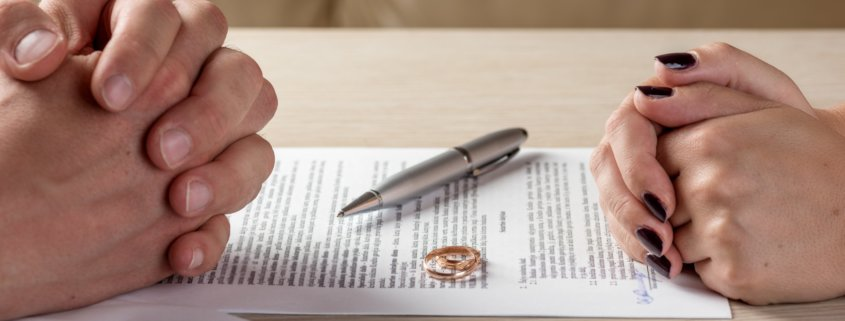 LPEP Law helps a couple with the divorce question of dividing property after a divorce. Two rings on the table between the clients.