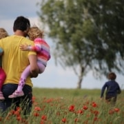 A father granted custody, thanks to fathers rights, holds his children on a walk outside.