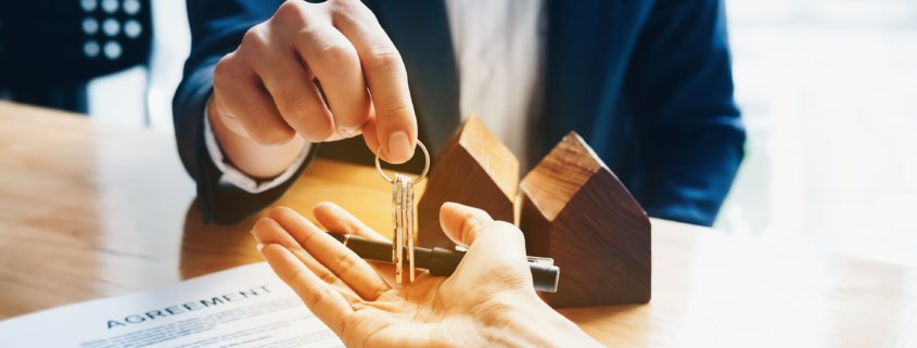 An attorney hands over keys to a property that was listed in the revocable living trust to the beneficiary.