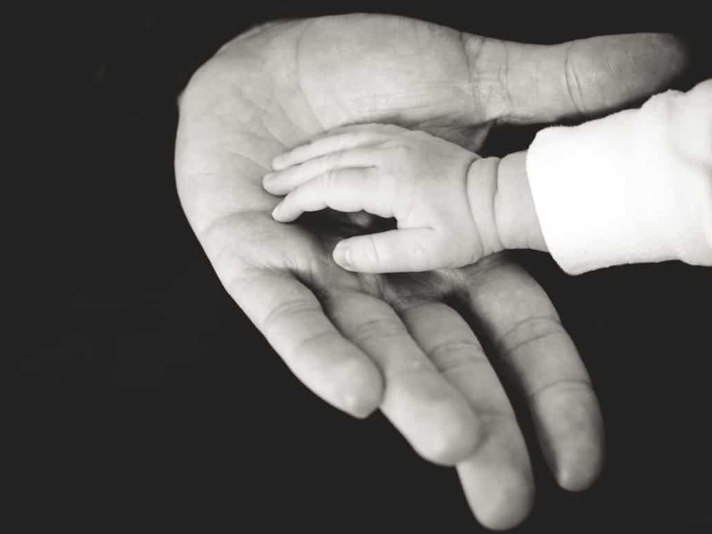 Grandparent holding babies hand. Learn about grandparents rights to child custody