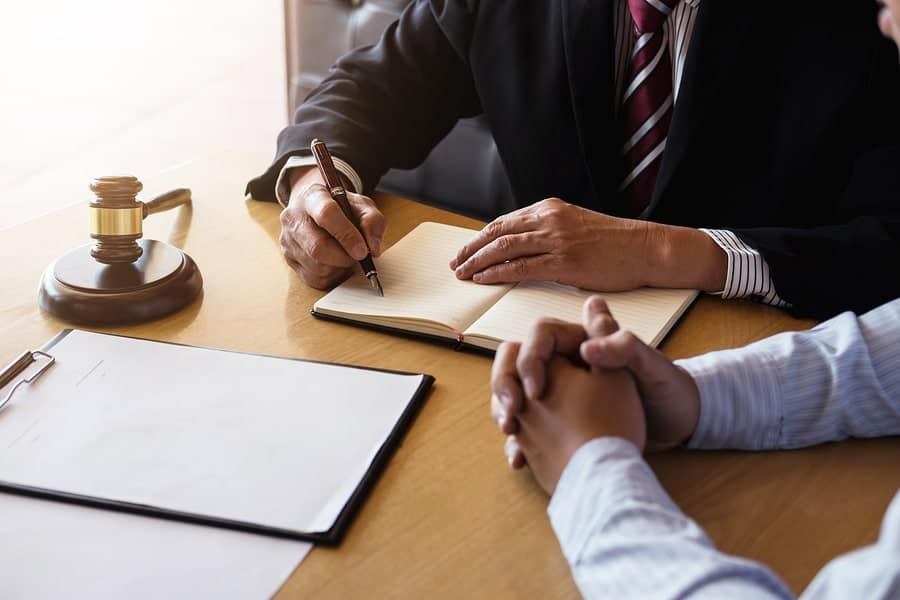 A child custody lawyer takes notes in a meeting with his client