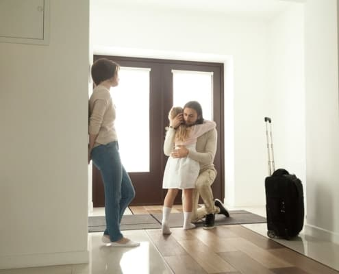 A father moves and hugs his kid after working with a parental relocation attorney to establish new custody stipulations.