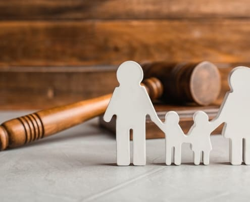 A statue of a family stands in front of a gavel in a Bay Area Family Law Courthouse .