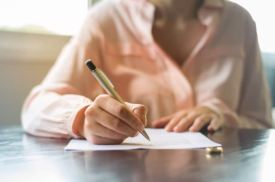A spouse signs divorce documents laid out by a divorce planning attorney.
