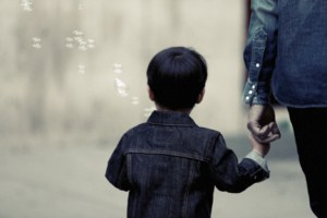 A small child holds its parent's hand after a child custody lawyer protected the parents rights to custody.