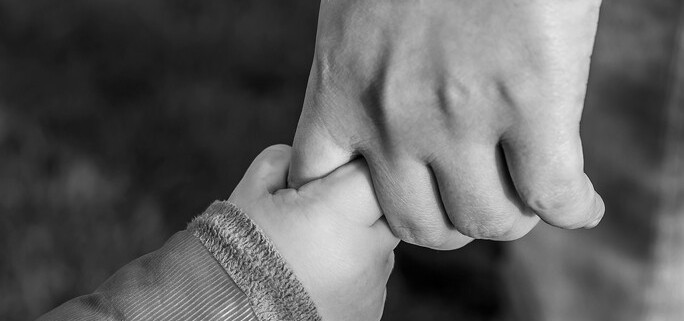 A black and white photo of a parent holding a child's hand after getting child custody