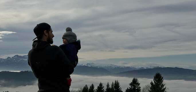 A parent in a backwards baseball cap holds their child overlooking a mountain after their parental relocation