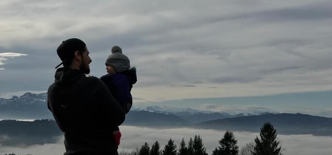 A parent with shared custody holds their child as they overlook the mountains