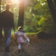 Father and child walk through the forest after he requests child support modification from courts