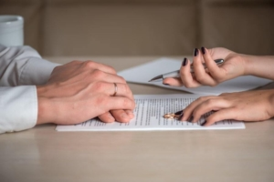 A spouse hands a pen to their partner as they sign a postnuptial agreement together