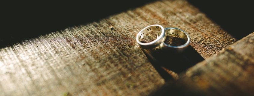 A married couple's rings sit on a wooden table as they contemplate a postnuptial agreement