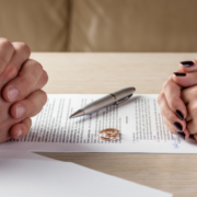 A couple sits opposite each other over paperwork discussing collaborative divorce vs mediation