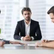 A couple sits at a table with a divorce mediation lawyer looking over paperwork