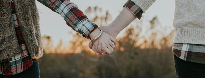 A same sex couple with spousal benefits holds hands in a field