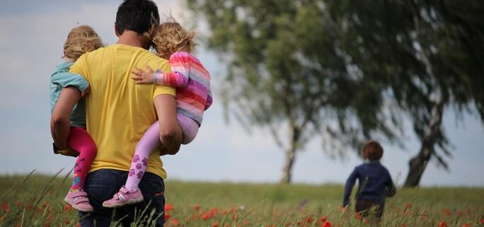 A father granted paternity holds two children as a third runs ahead through a field of flowers