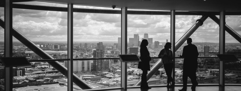 3 business owners meet in a building overlooking skyscrapers to discuss succession planning